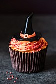 A halloween cupcake with orange buttercream an a witches' hat