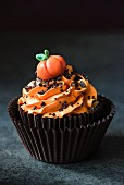A halloween cupcake with orange buttercream icing and a pumpkin