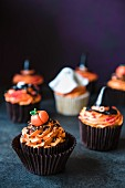 Halloween cupcakes with orange buttercream and assorted fondant decorations