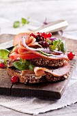 A slice of bread topped with ham, vegetables, lingonberries and chia seeds