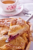 Plum pie with a slice removed (close-up)