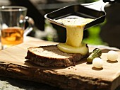 Raclette with bread, gherkins and pearl onions