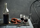A table scene with red wine and chorizo