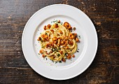Pasta spaghetti with wild forest mushrooms Chanterelle on white plate on wooden table