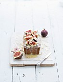 Loaf cake with figs, almond and white chocolate on white serving board over white wooden background