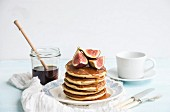 Homemade pancaces tower with fresh figs and honey on white plate over white wall background