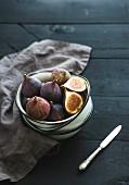 Fresh figs in white metal bowls over dark wooden background