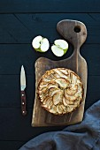 Homemade apple pie served with fresh apples on rustic wooden board over dark wooden backdrop