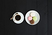 Cup of espresso and sweet colorful French macaroon biscuits over dark wooden backdrop