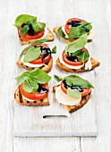 Toasted bread with tomato, mozzarella, basil and balsamic vinegar on a wooden board painted white