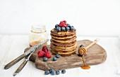 Turm aus Pancakes mit frischen Beeren und Honig auf Holzbrett
