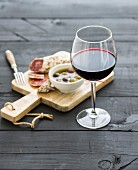 Glass of red wine, French sausage and olives on black wooden backdrop