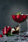 A coupe glass of Raspberry and Pomegranate Champagne Cocktailed garnished with mint