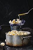 Popcorn mit geschmolzener Butter und Meersalz in Vintage Aluminiumtopf und in kleinem Eimer