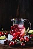 Limonade mit Kirschen und Limetten, serviert in Glaskanne mit Eiswürfeln