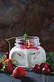 Square glass jar with homemade yogurt with mint, strawberry puree and cherry, served with fresh berries
