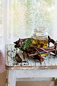 Glass jar of hot herbal tea with bunch of fresh thyme, served with vintage tea-strainer