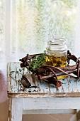 Kräutertee mit Thymian im Glas, serviert mit Vintage-Teesieb auf altem Holzhocker vor Fenster