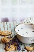 Lavender cookies and bowl of aromatic milk, served with kitchen towel on old wooden table