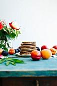 Gestapelte Pancakes umgeben von Früchten auf türkis Holztisch