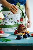 Gestapelte Pancakes mit Früchten und mit Honig begiessen
