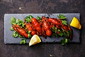 Red boiled crayfish with lemon on stone slate on dark background