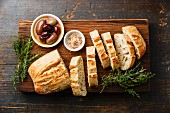 Fresh Ciabatta bread cut in slices on wooden cutting board with olives and herbs on rustic wooden background