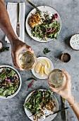 Paniertes Fischfilet mit Salatbeilage, Hände stossen mit Weissweingläsern an