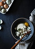 Ricotta soft cheese in a mixing bowl with eggs and herbs