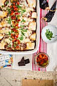 Enchiladas with pork and mole sauce in a baking dish with pickled jalapenos