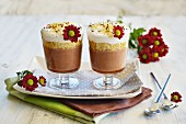Chocolate, cereal and coconut milk desserts in two serving glasses standing next to each other and decorated with fresh flowers