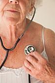 Elderly woman using a stethoscope