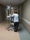 Nurse wheeling patient along corridor