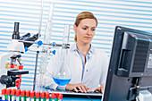 Female chemist using computer in lab