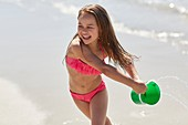 Girl playing on beach with bucket