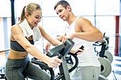 Man instructing woman in gym