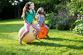 Two sisters bouncing on bouncy hoppers