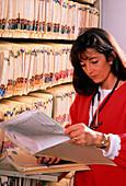 Nurse checks medical records in a filing room