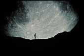 Composite image of Moon behind silhouetted person