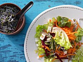 A salad with beetroot, carrot, sheep's cheese and beansprouts