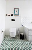 Toilette und Badewanne im Badezimmer mit grün-weiss gemusterten Bodenfliesen