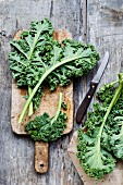 Curly kale on a wooden board with a knife