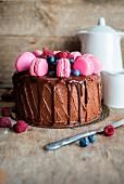 Schokoladenkuchen mit tropfender Schokoladenganache, frischen Beeren und rosa Macarons