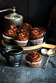 Schokoladencupcakes mit Schokoladen-Frosting und eine Tasse Kaffee