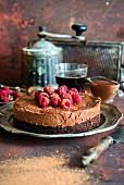 Schokoladenmoussetorte mit Biskuitboden, Himbeeren und Kakaopulver