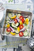 Fresh vegetables in a roasting tin (courgette, onions, tomatoes, yellow pepper, garlic and thyme)
