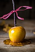 A toffee apple on a wooden surface