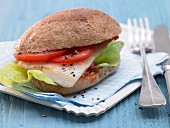 A fish burger with chilli sauce, tomatoes and salad