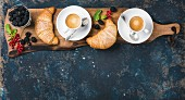 Freshly baked croissants with garden berries and coffee cups served on rustic wooden board