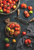 Fresh colorful ripe Fall heirloom tomatoes in basket, herb chopper knife
